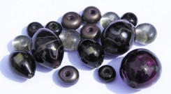 Beads made from transparent purple, transparent grey, and metallic opaque grey glass.