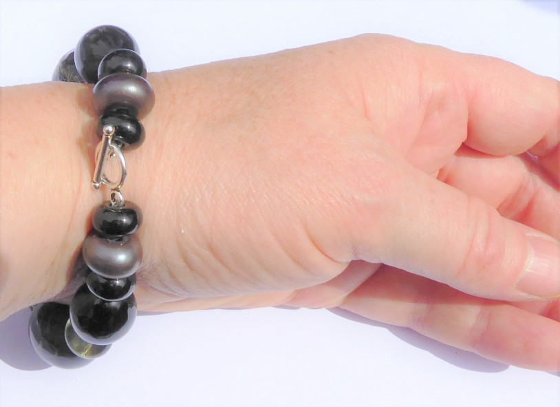 ouble-threaded with tiger tail, fixed with crimp beads and a clasp.