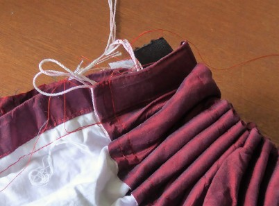 Silk curtain was already hemmed at the bottom and had curtain tape at the top so I had a good headstart on a skirt. I turned the curtain tape over and stitched it down to make a hollow waistband and ran some thick elastic through. Then I did the side seam, stitching over the elastic also to hold it in place.