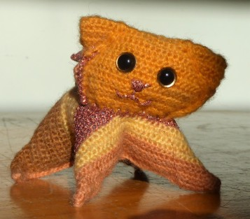 This kitty is made to the cat pattern, but in a yarn finer than DK. It's self-striping dy choice SPARKLZ. Yeah. His head's on a bit tilted, but it gives him some life.