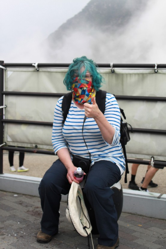 When the sulphur fumes mixed with the rain, time to use my headband as a face mask. I am sitting on a black egg chair.