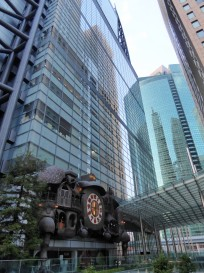 A steampunk clock crouching among the high rises near the hotel.