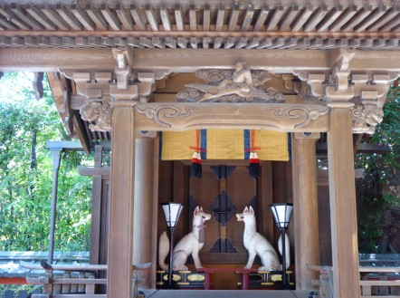 Two smaller, finely-carved foxes in a shrine.