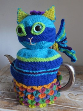 A teacosy made for friends, that ended up being a rainbow mercat. Working the shaping in dragon scale stitch for the tail was challenging, but I like the way she turned out.