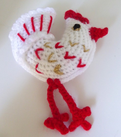 The chicken is made by starting with a standard amigurumi circle pattern, and overdoing the increases. You end up with a frilly circle. When you fold it in half you get a crescent - ideal as a birdy base.